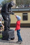 Młoda chłopiec uderza pięścią pięści z żywą statuą Zdjęcie Royalty Free