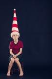 Młoda chłopiec w czerwonej i białej pasiastej dunce nakrętce Obrazy Royalty Free