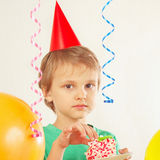 Młoda chłopiec w wakacyjnym kapeluszowym łasowanie kawałku urodzinowy tort Obrazy Stock