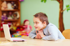 Młoda chłopiec z dodatkiem specjalnym potrzebuje dopatrywanie środki przez laptopu obrazy royalty free