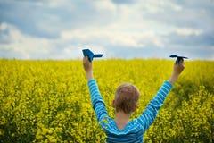 Młoda chłopiec z papieru samolotem przeciw niebieskiemu niebu Śródpolny Flo i kolorowi żółtemu Zdjęcia Stock