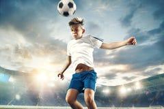 Młoda chłopiec z piłki nożnej piłką robi latającemu kopnięciu przy stadium obraz royalty free