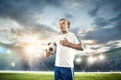Młoda chłopiec z piłki nożnej piłką robi latającemu kopnięciu przy stadium zdjęcie royalty free