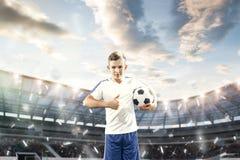 Młoda chłopiec z piłki nożnej piłką robi latającemu kopnięciu przy stadium zdjęcia royalty free
