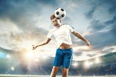 Młoda chłopiec z piłki nożnej piłką robi latającemu kopnięciu przy stadium zdjęcia stock