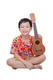 Młoda chłopiec z ukulele nad bielem Fotografia Stock