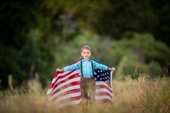 Młoda chłopiec z wielką flaga amerykańską pokazuje patriotyzm dla jego swój kraju, Jednoczy stany zdjęcie royalty free