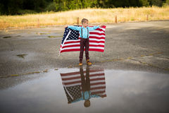 Młoda chłopiec z wielką flaga amerykańską pokazuje patriotyzm dla jego swój kraju, Jednoczy stany Zdjęcie Stock
