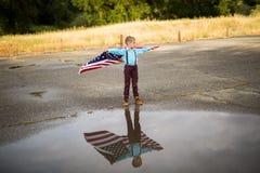 Młoda chłopiec z wielką flaga amerykańską pokazuje patriotyzm dla jego swój kraju, Jednoczy stany Obraz Royalty Free