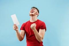 Młoda chłopiec z zdziwionym wyrażenie zakładu ślizganiem na błękitnym tle fotografia royalty free