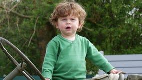 Młoda chłopiec z zielony puloweru bawić się plenerowy zdjęcie wideo