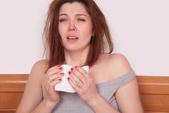 Młoda chora kobieta z czerwonym nosa obsiadaniem w łóżku i kichnięciu Zdjęcie Stock