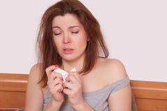 Młoda chora kobieta z czerwonym nosa obsiadaniem w łóżku i kichnięciu Zdjęcie Royalty Free