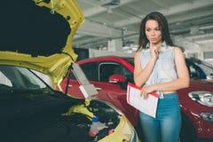 Młoda ciemnowłosa kobieta egzamininuje samochód przy przedstawicielstwem handlowym i robi jego wyborowi Zdjęcia Royalty Free