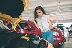 Młoda ciemnowłosa kobieta egzamininuje samochód przy przedstawicielstwem handlowym i robi jego wyborowi Zdjęcie Royalty Free