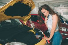 Młoda ciemnowłosa kobieta egzamininuje samochód przy przedstawicielstwem handlowym i robi jego wyborowi Obrazy Royalty Free