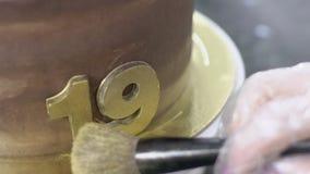 Młoda cukierniczka stawia proszek na czekoladowych liczbach na torcie w kuchni indoors zdjęcie wideo