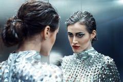 Młoda cyber kobieta w srebny futurystyczny kostiumowy patrzeć w lustrze Fotografia Stock