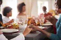 Młoda czarna dorosła kobieta i córki mienia ręki mówić przy dziękczynienie łomotem gracja z ich wielo- pokolenie rodziną i zdjęcie stock