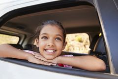 Młoda czarna dziewczyna przyglądająca z samochodowego okno ono uśmiecha się up zdjęcia stock