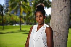 Młoda czarna kobieta pozuje drzewem w parkowym jest ubranym kolii włosianej babeczki rozmytym tle zdjęcia royalty free