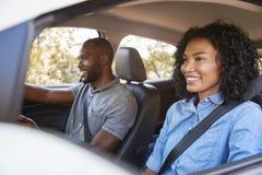 Młoda czarna para naprzód ono uśmiecha się w samochodzie na wycieczki samochodowej spojrzeniu fotografia stock