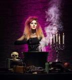 Młoda czarownica robi guślarstwu w Hallowen dungeon obraz royalty free