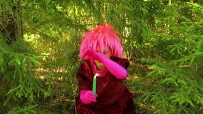 Młoda czarownica siedzi w drewnach i czyta czary nad płonącą świeczką zbiory wideo