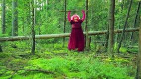 Młoda czarownica w czerwieni w lesie przekręca jego personelu nad jego głową zdjęcie wideo