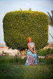 Młoda czerwona kobieta na ławce Fotografia Stock