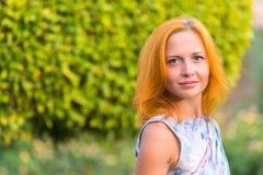 Młoda czerwona kobieta na ławce Zdjęcia Stock
