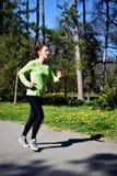 Młoda czerwona włosiana dama w zielonej koszula robi ona biega szkolenie w parku 1 zdjęcia royalty free