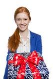 Młoda czerwona z włosami dziewczyna przedstawia prezent Zdjęcia Stock