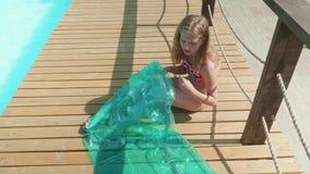 Młoda długowłosa blondynka chucha up materac basenem zbiory