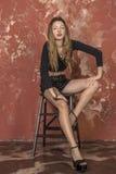 Młoda długowłosa długonoga chuderlawa dziewczyna w skrótach i estradowych sandałach czarnego puloweru i skóry Obrazy Royalty Free