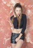 Młoda długowłosa długonoga chuderlawa dziewczyna w skrótach i estradowych sandałach czarnego puloweru i skóry Zdjęcie Stock