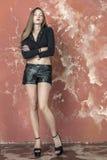 Młoda długowłosa długonoga chuderlawa dziewczyna w skrótach i estradowych sandałach czarnego puloweru i skóry Obraz Royalty Free