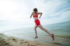 Młoda dama bieg przy pogodną lato piaska plażą trening jogger obrazy royalty free