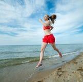 Młoda dama bieg przy pogodną lato piaska plażą trening jogger zdjęcia royalty free