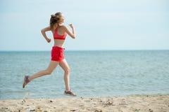 Młoda dama bieg przy pogodną lato piaska plażą trening jogger obraz royalty free