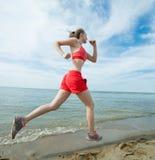 Młoda dama bieg przy pogodną lato piaska plażą trening jogger obraz stock