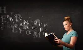 Młoda dama czyta książkę z abecadło listami obraz stock