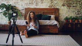 Młoda dama jest magnetofonowym wideo dla onlinego vlog pokazuje i opowiada smartphone i fotografie dyskutujący ilość zbiory