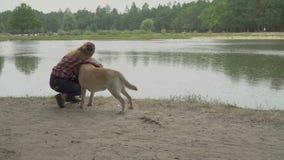 Młoda dama muska jej psa blisko rzeki zbiory wideo