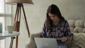 Młoda dama płaci dla zakupów w online sklepie podczas gdy siedzący w mieszkaniu zdjęcie wideo