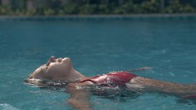 Młoda dama relaksuje dopłynięcie na plecy w jasnym błękitnym basenie zbiory
