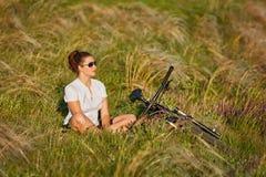 Młoda dama relaksuje na zielonej łące po jeździć na rowerze Obrazy Stock