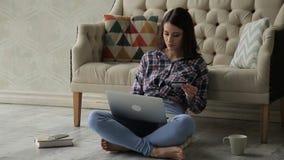 Młoda dama siedzi skrzyżnego i typ jej laptop w jaskrawym pokoju jej numer karty kredytowej zbiory wideo