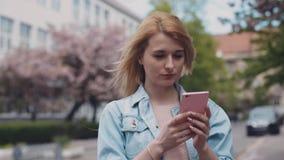 Młoda dama w cajgi kurtka, używa jej telefon w mieście Miastowi budynki, samochody na tle, wietrzna pogoda zdjęcie wideo