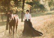 Młoda dama w rocznik sukni z długim pociągiem, spacery z koniem przez lasowych halizn Antyczna, zbierająca fryzura, fotografia royalty free